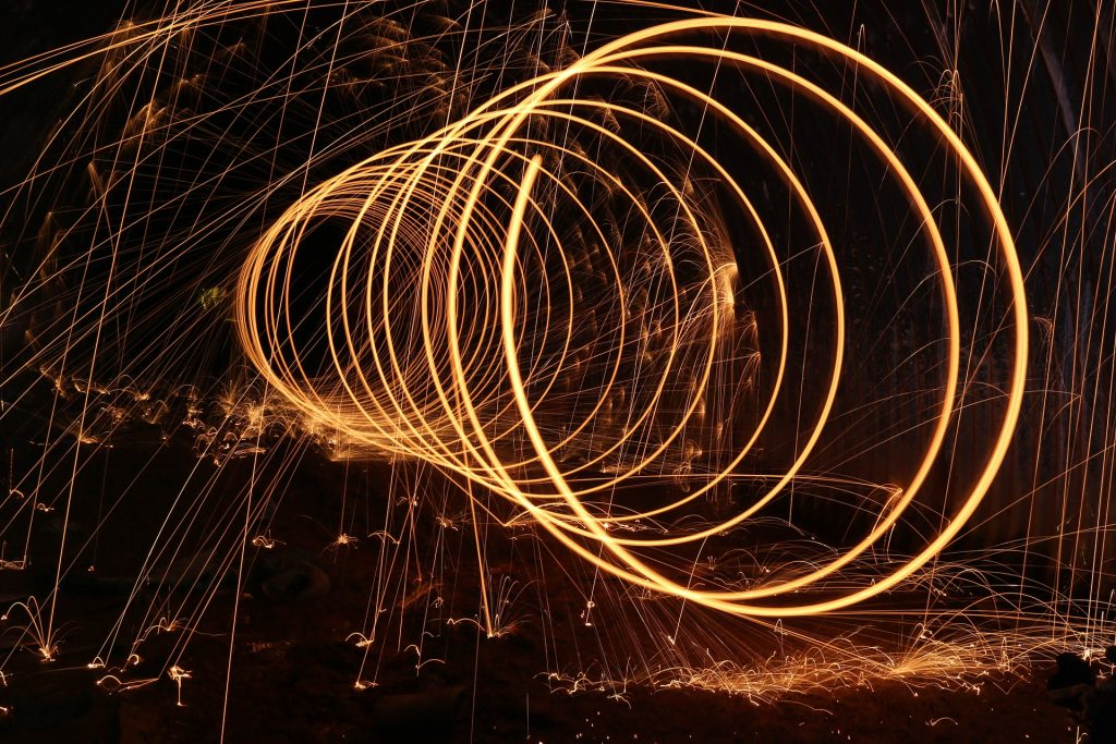 Long exposure photo of glowing fire being spun in spiral.